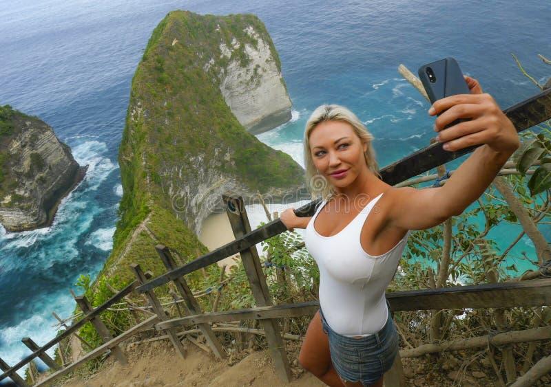 Mulher loura atrativa e feliz nova do turista que toma o selfie no ponto de vista bonito da praia do penhasco do mar que aprecia  fotografia de stock