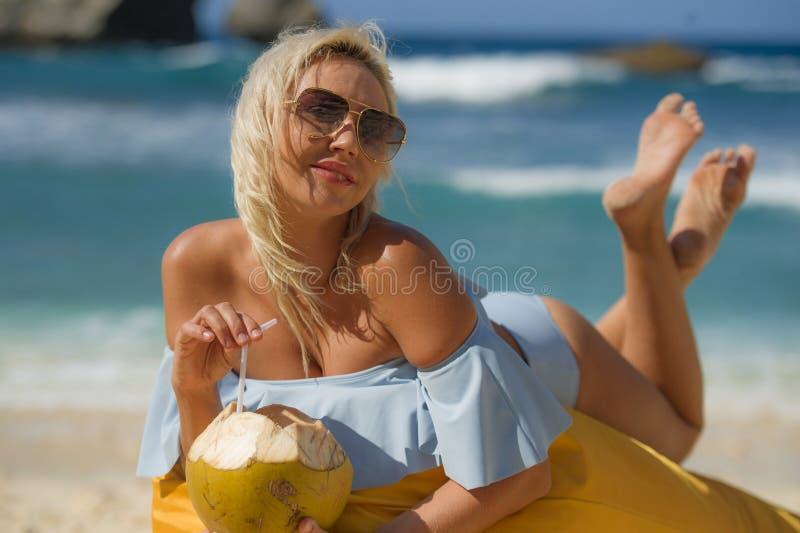 Mulher loura atrativa e relaxado nova no biquini que encontra-se na rede do beanbag na água bebendo do coco da praia tropical do  imagem de stock royalty free