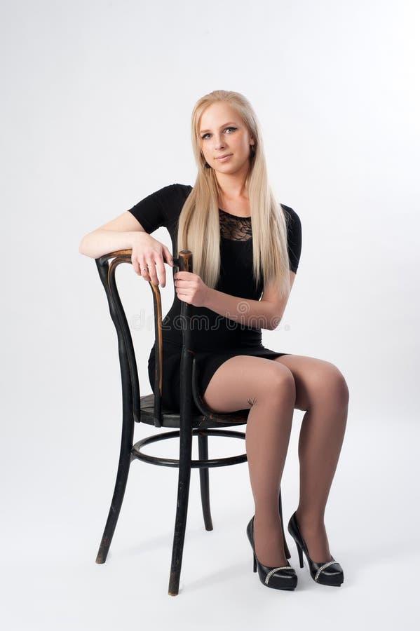 Mulher loura atrativa na cadeira fotografia de stock