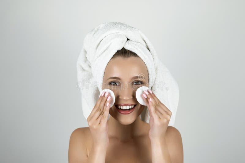 Mulher loura atrativa na toalha branca em sua cabeça que guarda almofadas de algodão perto de seu fundo branco isolado cara fotografia de stock