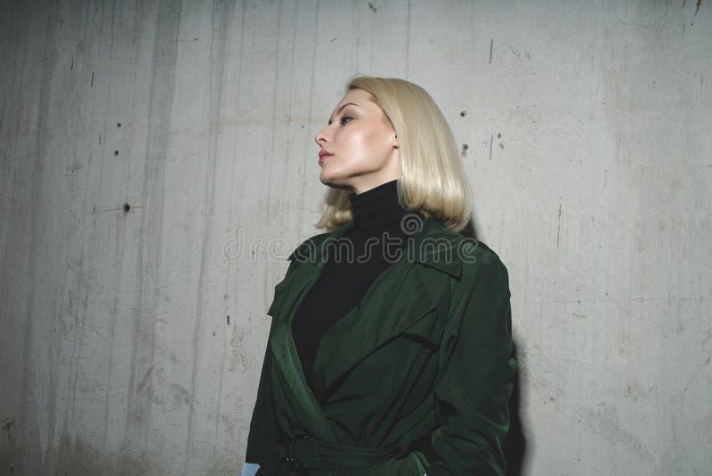 Mulher loura atrativa no revestimento verde contra um muro de cimento fotografia de stock