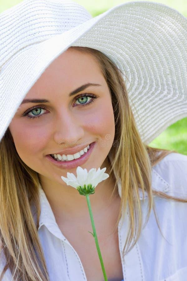 Mulher loura atrativa nova ao guardarar uma flor branca imagem de stock