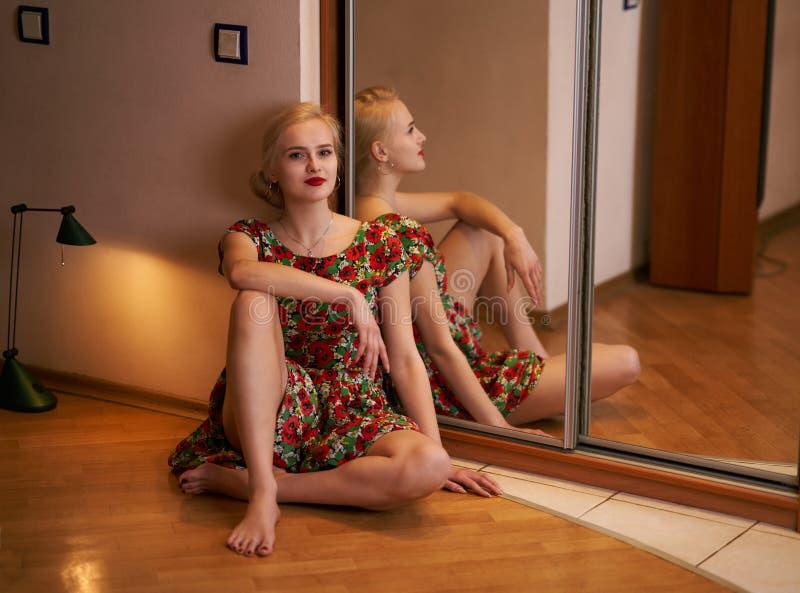 Mulher loura atrativa nova que levanta o assento no assoalho em um hotel perto do espelho fotografia de stock royalty free