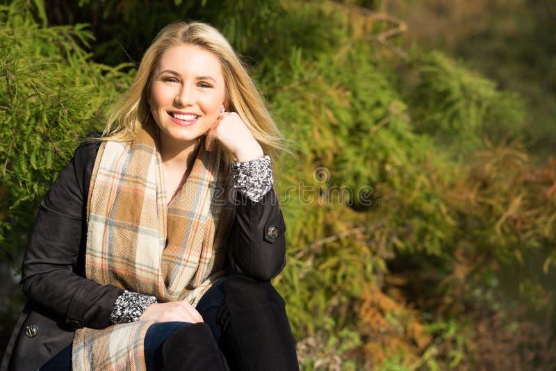 Mulher loura atrativa que aprecia o sol do outono foto de stock