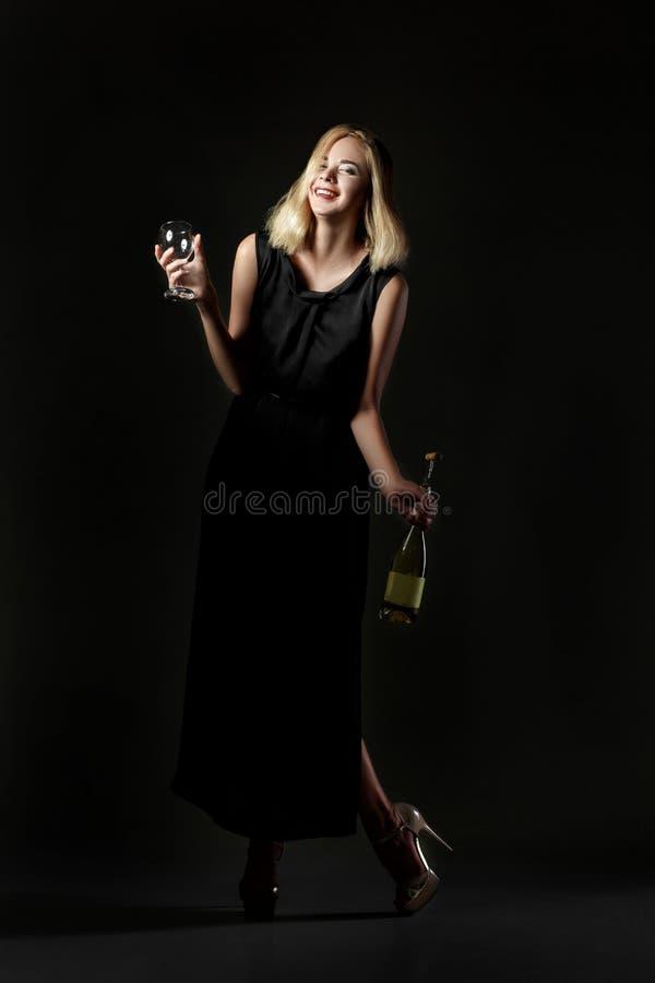 Mulher loura bebida bonita que guarda a garrafa de vinho branco no fundo preto Partido e feriado imagens de stock