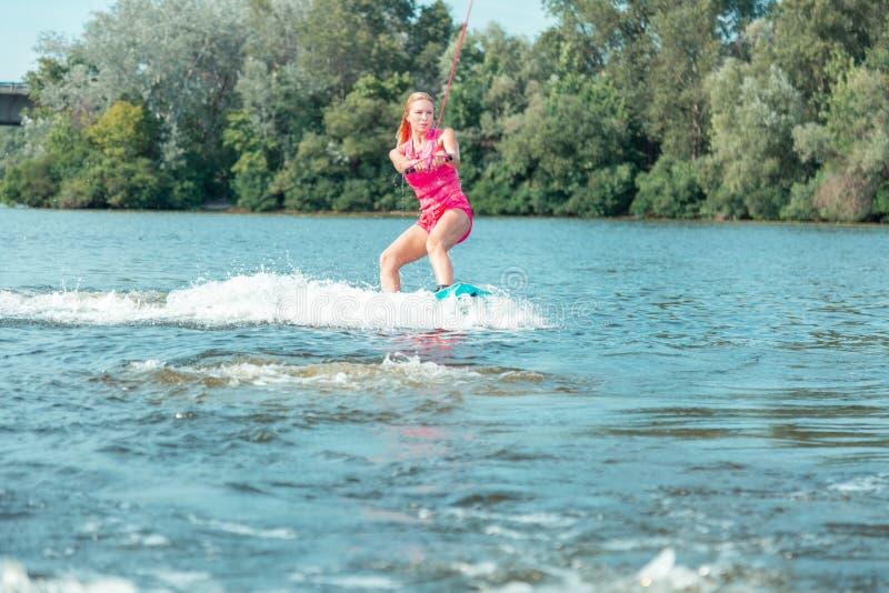 Mulher loura bonita ativa nova que monta um wakeboard imagem de stock
