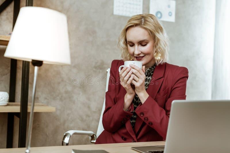 Mulher loura bonita calma e calma que leva o copo quente fotos de stock