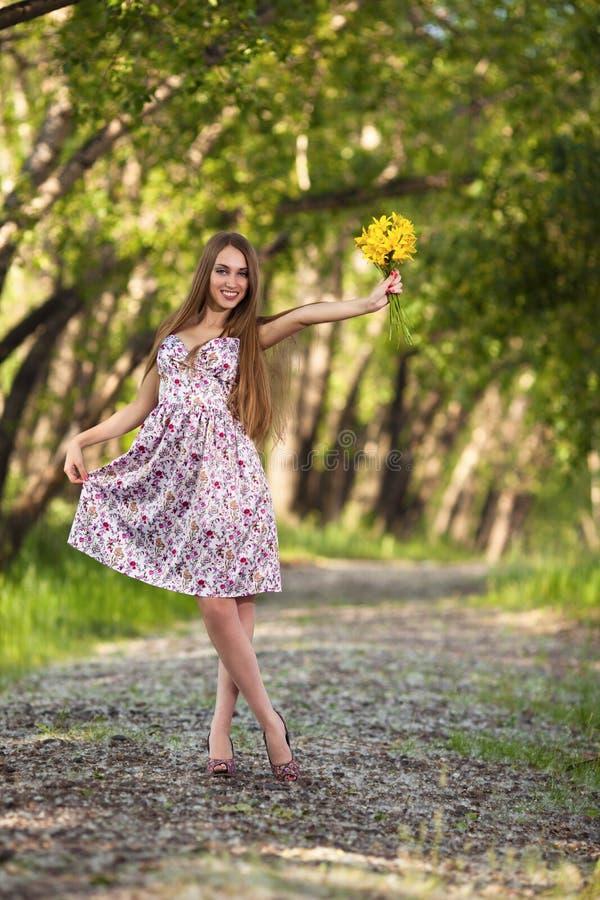 Mulher loura bonita com as flores amarelas ao ar livre fotografia de stock