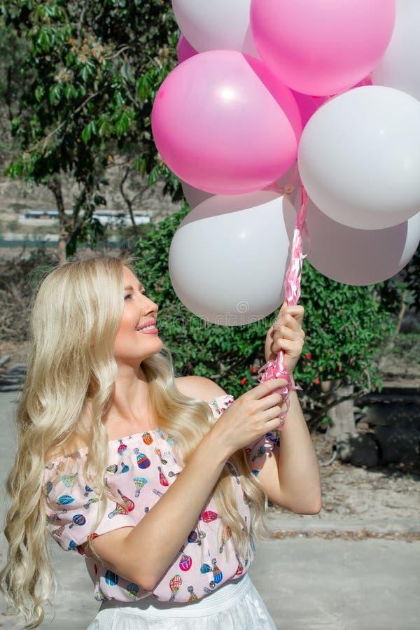 Mulher loura bonita, com balões, no rosa Sorriso e feliz, andando no parque fotos de stock royalty free