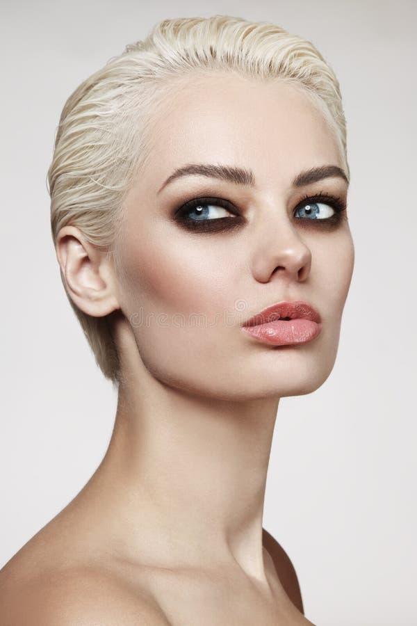 A mulher loura bonita com cabelo do duende cortou e o olho fumarento m fotografia de stock