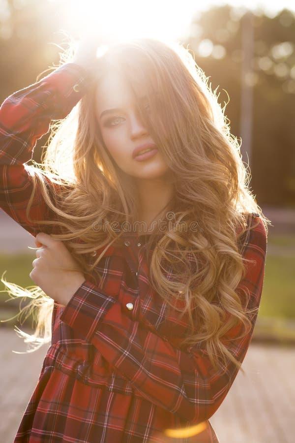 Mulher loura bonita com cabelo ondulado longo no checke elegante imagens de stock
