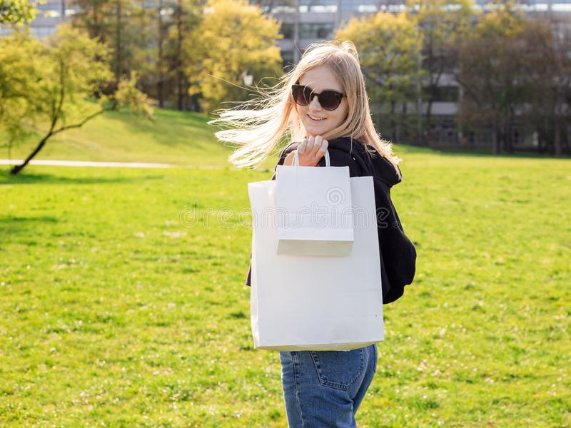 A mulher loura bonita com ?culos de sol aprecia a compra Consumi??o, zombaria de compra acima, conceito do estilo de vida foto de stock royalty free