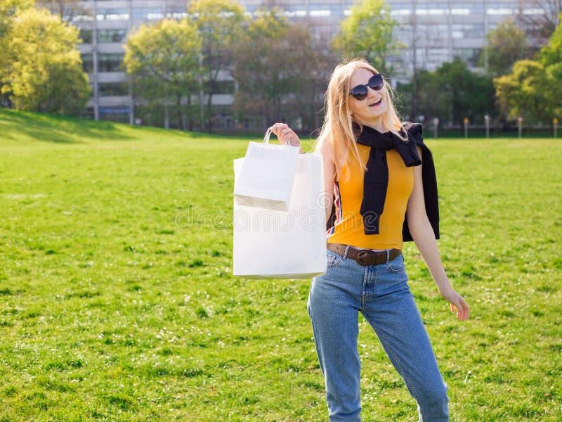 A mulher loura bonita com ?culos de sol aprecia a compra Consumi??o, zombaria de compra acima, conceito do estilo de vida fotografia de stock royalty free