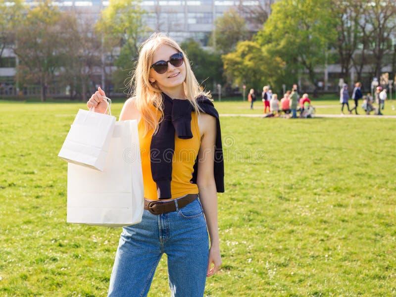 A mulher loura bonita com ?culos de sol aprecia a compra Consumi??o, zombaria de compra acima, conceito do estilo de vida fotos de stock royalty free