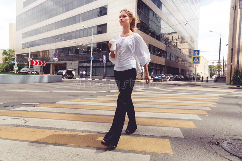 Mulher loura bonita com o café para ir cruzar a estrada imagens de stock royalty free