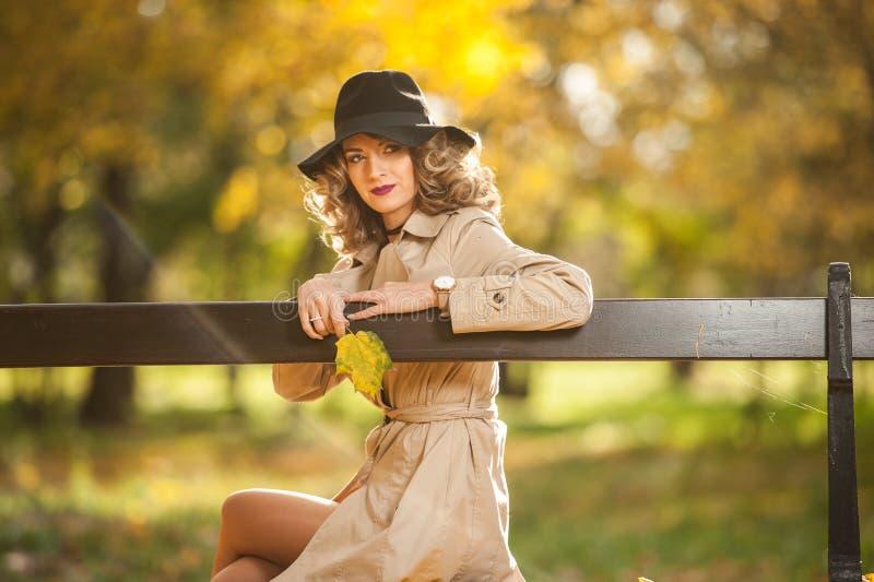 Mulher loura bonita com revestimento de creme, pés longos e chapéu negro em uma cena do outono imagem de stock royalty free