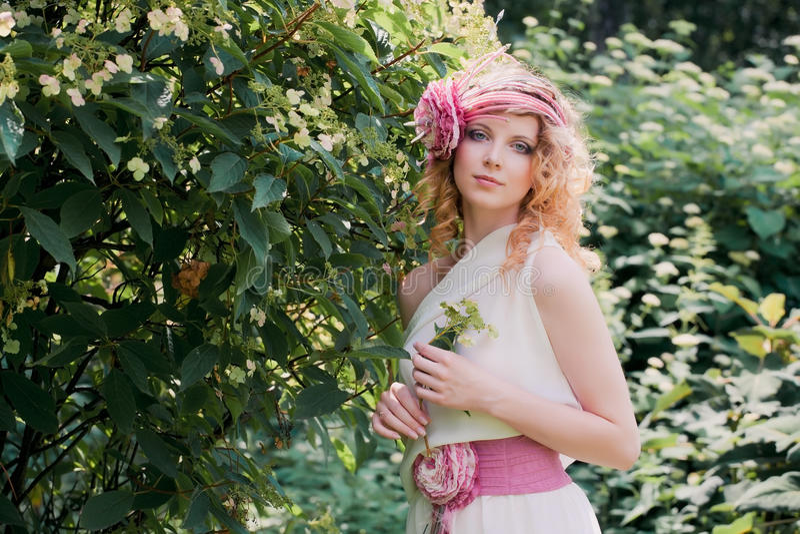 Mulher loura bonita com uma flor fotografia de stock royalty free