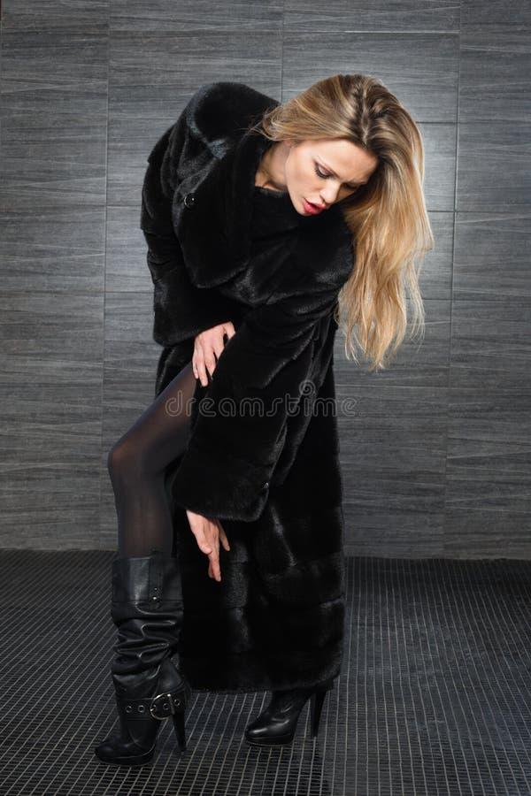 Mulher loura bonita da forma que levanta no casaco de pele Modelo da menina do inverno na roupa luxuosa e no colar peludo no fund imagem de stock royalty free
