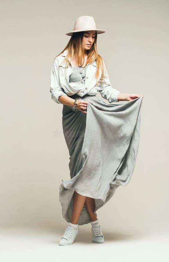 Mulher loura bonita de dança na camisa do vestido e da sarja de Nimes imagem de stock royalty free