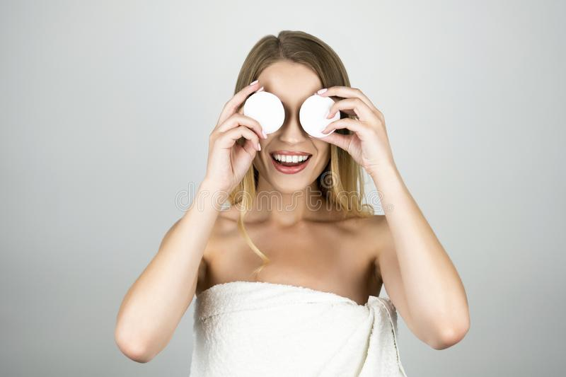 Mulher loura bonita de sorriso na toalha branca que aplica almofadas de algodão em seu fundo branco isolado olhos fotografia de stock royalty free