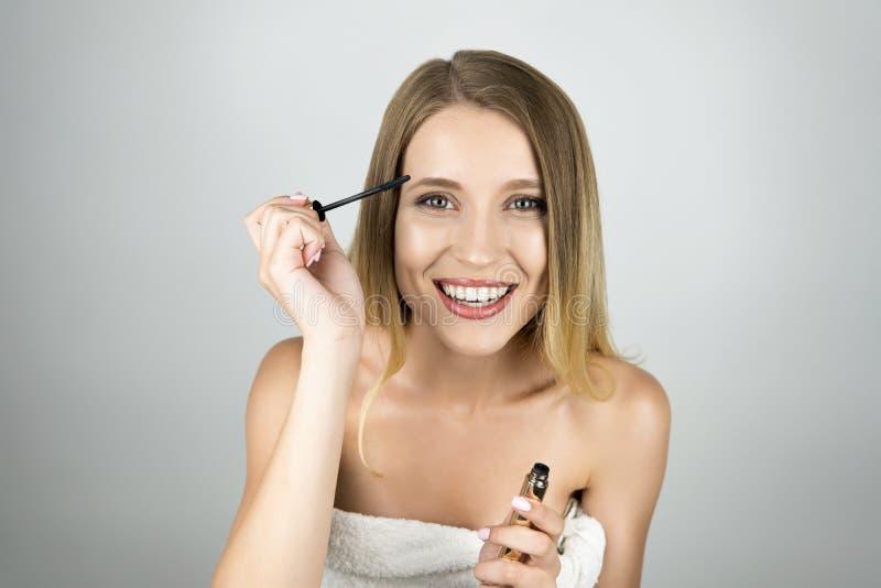 Mulher loura bonita de sorriso que aplica o fundo branco isolado rímel foto de stock royalty free