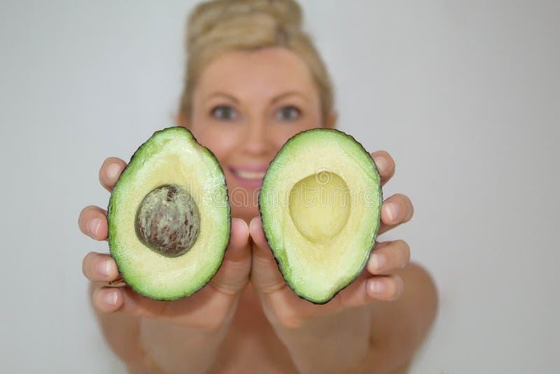Mulher loura bonita do abacate na frente da câmera, close-up fotografia de stock