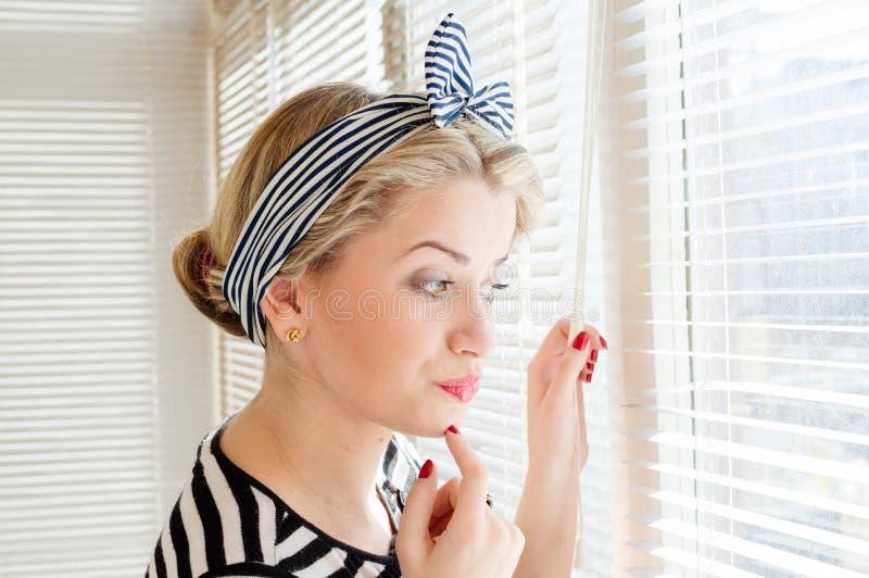 Mulher loura bonita do pinup que olha pensativamente através das janelas do jalousie imagem de stock