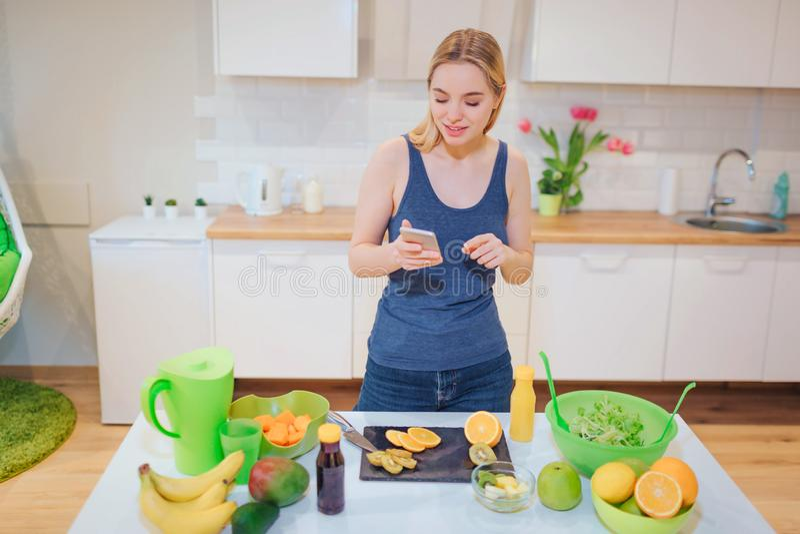 Mulher loura bonita do vegetariano com smartphone que fotografa a laranja orgânica na cozinha Alimento saudável Desintoxicação da imagem de stock royalty free