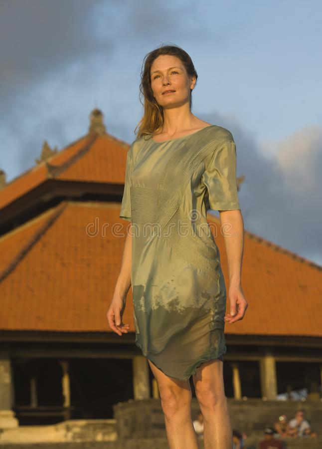 Mulher loura bonita e atrativa nova que levanta como o modelo de forma da beleza isolado na frente do templo asiático que veste o fotografia de stock