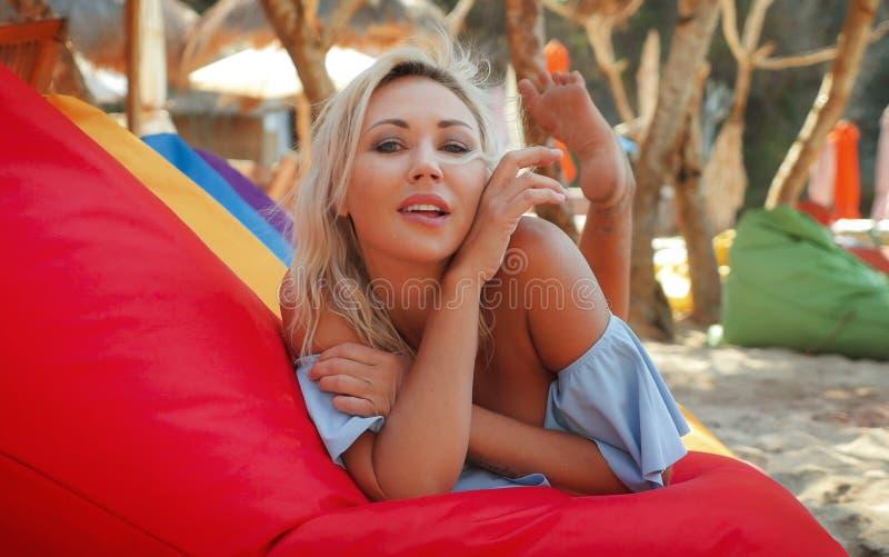 A mulher loura bonita e feliz nova com olhos azuis relaxou e refrigerou o encontro na rede do beanbag sob vestir do sol à moda fotos de stock