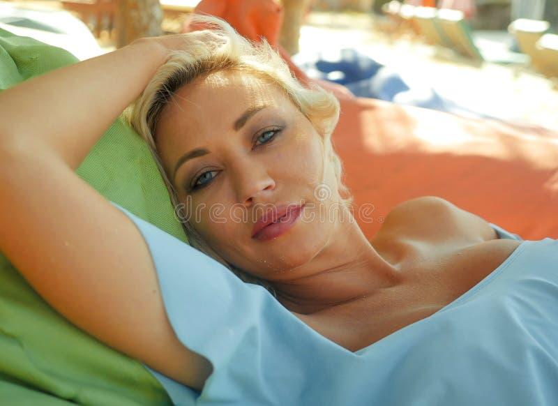 A mulher loura bonita e feliz nova com olhos azuis relaxou e refrigerou o encontro na rede do beanbag sob vestir do sol à moda fotos de stock royalty free