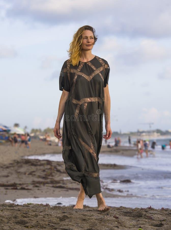 Mulher loura bonita e glamoroso feliz nova que levanta tão na praia que veste o sentimento alegre de sorriso do vestido à moda fr foto de stock