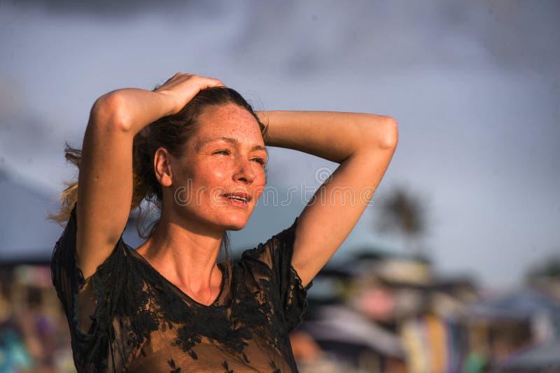 Mulher loura bonita e glamoroso feliz nova que levanta tão na praia que veste o sentimento alegre de sorriso do vestido à moda fr fotografia de stock
