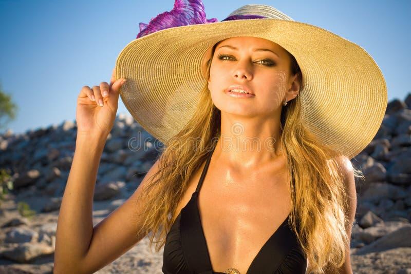 Mulher loura bonita em um chapéu em uma praia imagens de stock royalty free
