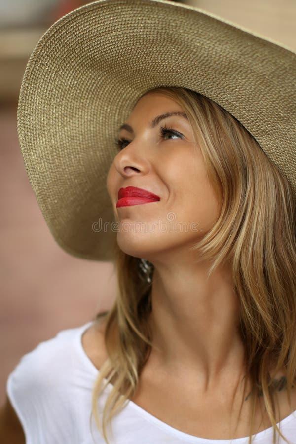 Mulher loura bonita em um chapéu que olha acima com bordos vermelhos em uma camisa branca de t fotos de stock royalty free