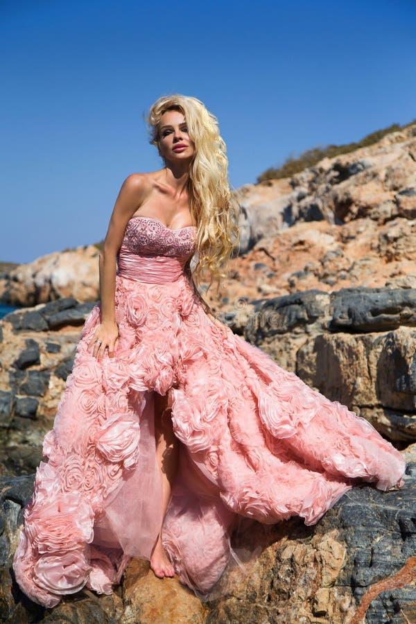 Mulher loura bonita em um vestido cor-de-rosa fabuloso que está nas rochas em Grécia fotografia de stock