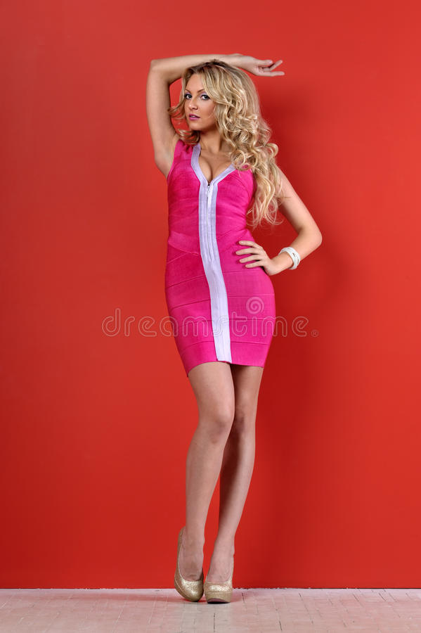 Mulher loura bonita em um vestido curto cor-de-rosa. fotografia de stock royalty free