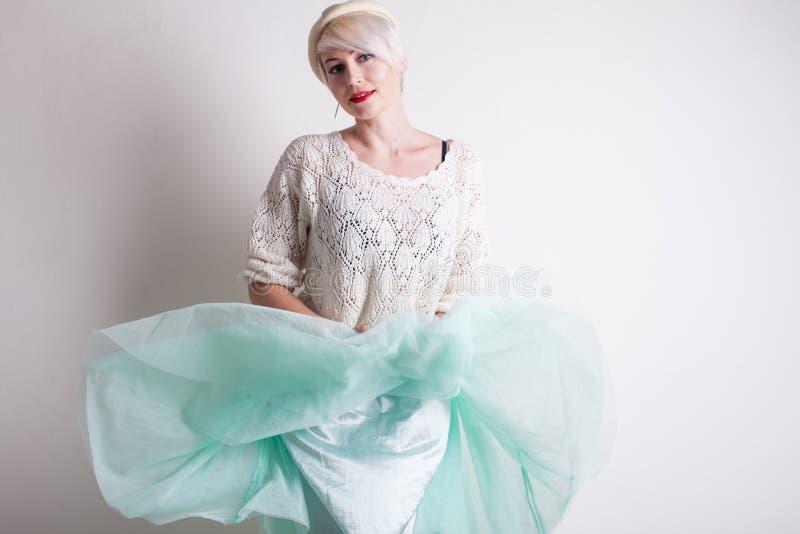 Mulher loura bonita em uma boina e em um vestido brilhante em um fundo branco foto de stock