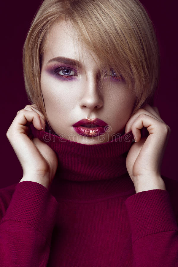 Mulher loura bonita em uma camiseta vermelha com composição brilhante e os bordos escuros Face da beleza imagem de stock royalty free