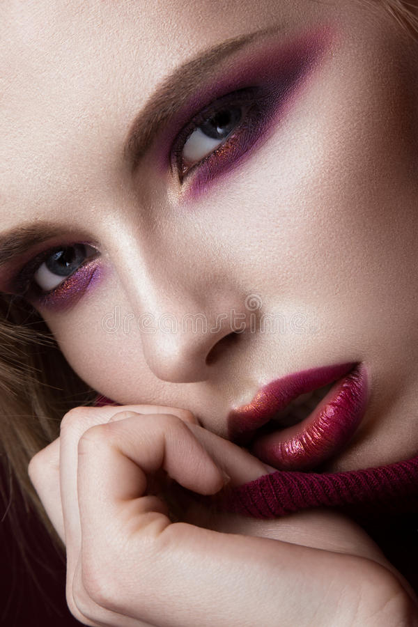 Mulher loura bonita em uma camiseta vermelha com composição brilhante e os bordos escuros Face da beleza Retrato do close-up fotografia de stock