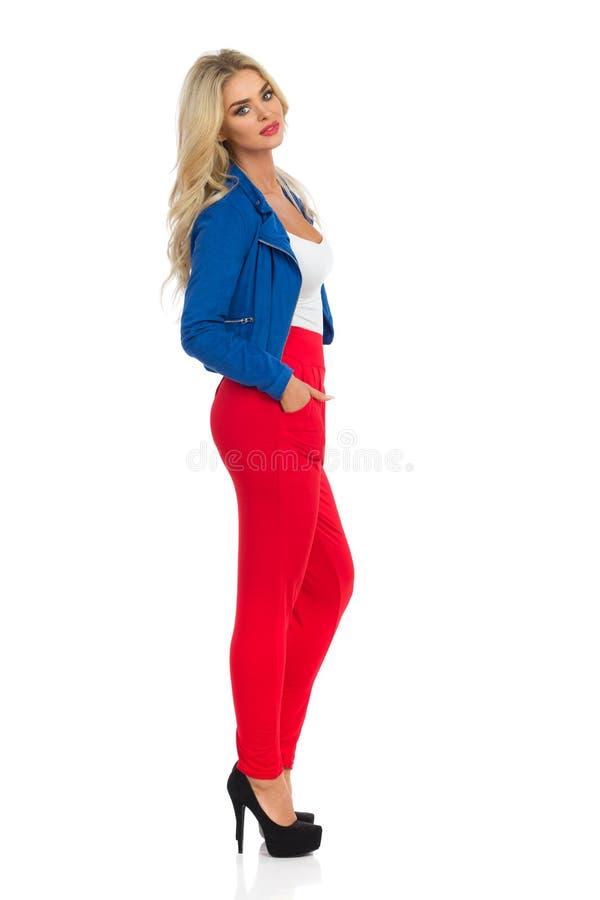 A mulher loura bonita está estando em calças, no casaco azul e nos saltos altos vermelhos Vista lateral fotos de stock royalty free