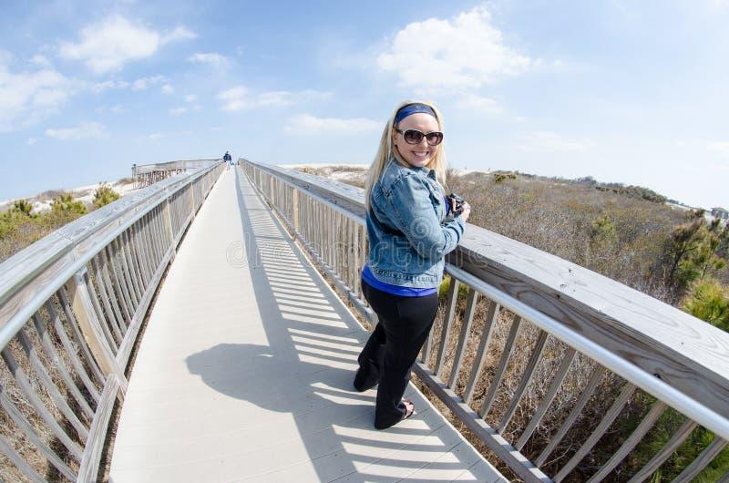 A mulher loura bonita está no passeio à beira mar elevado na ilha de Assateague foto de stock