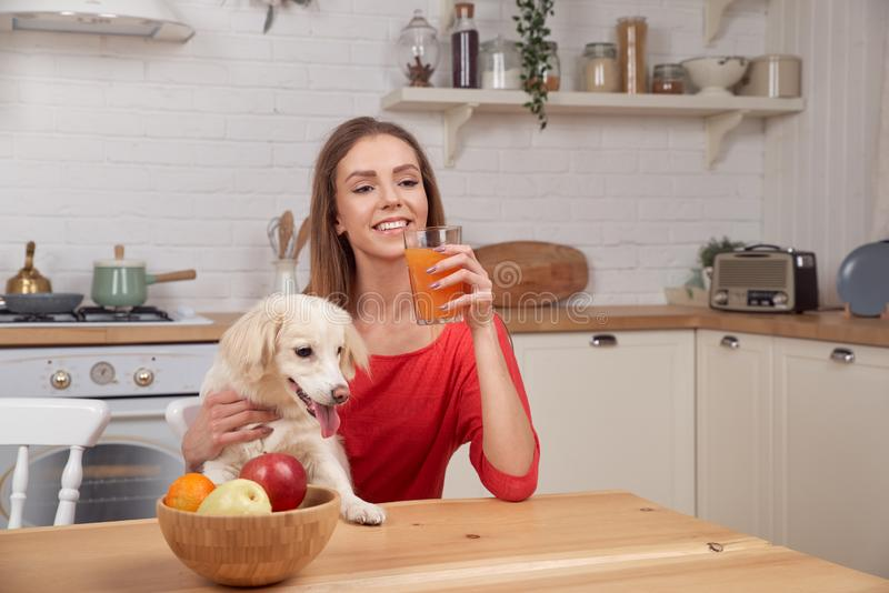 A mulher loura bonita está sentando-se na mesa de cozinha, suco de laranja bebendo, vestido na camiseta vermelha imagens de stock royalty free