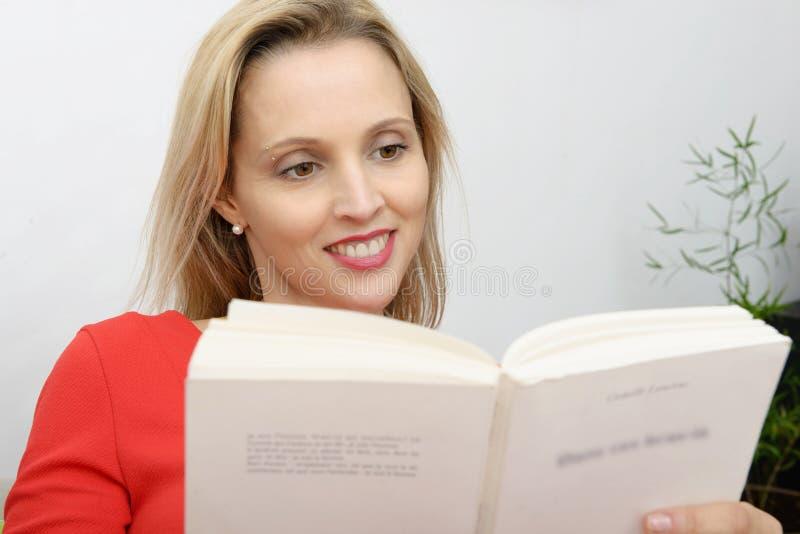 A mulher loura bonita lê um livro no sofá foto de stock
