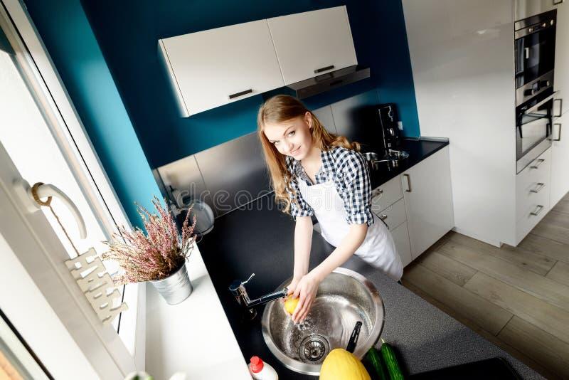 A mulher loura bonita lava os pratos imagens de stock