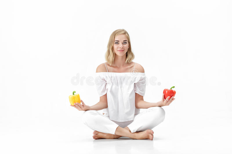 A mulher loura bonita na blusa branca escolhe a pimenta de sino amarela ou vermelha Saúde e dieta fotografia de stock royalty free