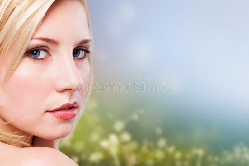 Mulher loura bonita na frente de uma cena da mola imagem de stock royalty free
