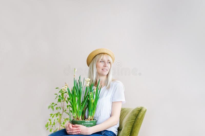 Mulher loura bonita no chapéu de palha que senta-se na cadeira verde com flor fotografia de stock