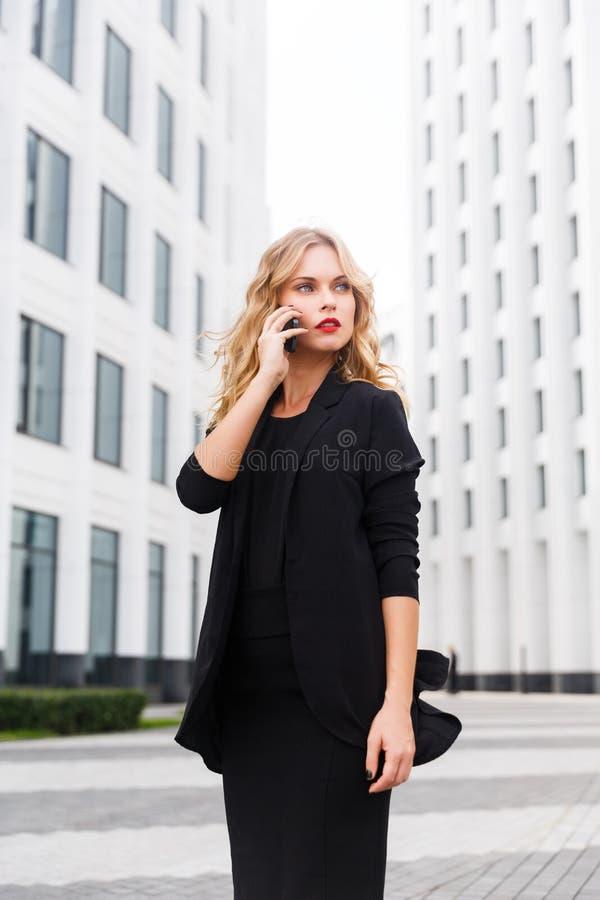 A mulher loura bonita no negócio preto veste a fala no telefone fotografia de stock