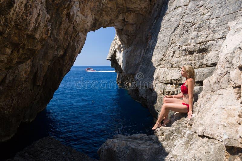 A mulher loura bonita no roupa de banho vermelho senta-se em rochas litorais, mar azul e o fundo de pedra da caverna e um barco a fotos de stock royalty free